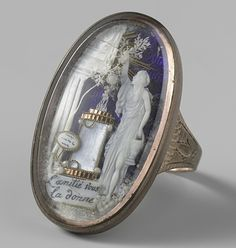 """Ring depicting a woman who sacrifices on the altar of love; mother of pearl on blue ground. Inscription of """"l'amite vous la donne."""" Circa 1785-1800"""