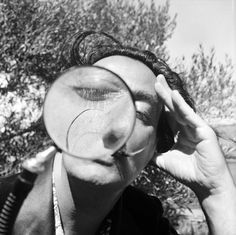 Salvador Dali (1904–1989) viewing the camera through a magnifying glass at his home in Cadaques on the Spanish Costa Brava, 1955. Photo by Charles Hewitt