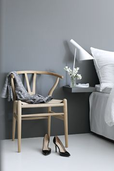 Wishbone chair and a grey wall in the bedroom of a serene Norwegian home on a hill. Nina Holst.
