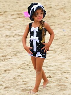 This 2 piece suit features a tank style top with center ruffle and bows. Bottoms are cut to create a perfect fit complete with center ruffle on each leg and...more bows! Matching hat has lots of shearing and center bow in a white fabric with tiny scattered black dots.    Size:  12M - 10    Licorice Twist Swimsuit $64.00