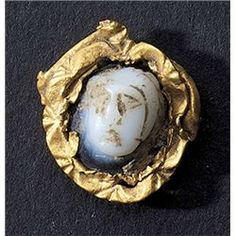 Engraved Gems & Cameos. Onyx cameo set in gold. Roman, Balkan region, circa 2nd- 3rd century AD. D/ Stylized mans head with hair realized with thin incisions. The gem is surrounded by scrolls made of gold sheet.