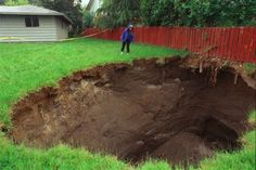 A neighbor checks out one of three large sinkholes to appear in an Everett, Wash., neighborhood on June 6, 1999. Photo: Scott Eklund/Seattle Post-Intelligencer