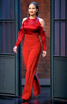 Jennifer Lopez in a cold-shoulder red top and high-waisted pants by Cushnie et Ochs