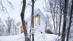 Naturehumaine designed the Poisson Blanc cabin in Laurentides, Québec with the striking shape to take cues from the rocky, inclined site. The wooden cladding is painted white to match the titanium coating on the roof, shown covered in snow this photo. Chalet Design, House Design, Architecture Design, Simple Dining Table, White Cabin, Wooden Cladding, Geometric Pendant Light, Basement Floor Plans, Glass Front Door
