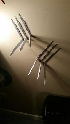 DIY Halloween Wolverine Claws Through The Wall - Want to make it look like Wolverine just slashed through your wall? Now you can for less than 10 dollars!! Materials: Craft foam sheets (2X), Paperclips (12X), Super Glue, Chrome Spray Paint, Scissors, Printer and computer, Cardboard