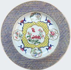 Assiette peinte dans les émaux de la famille rose en porcelaine de Chine de la Compagnie des Indes d'époque Yongzheng marquée Chenghua. Peinte dans les émaux de la famille rose, à décor de médaillons polylobés renfermant des paysages et encadrant un fond d'alvéoles jaunes. Sur l'aile, un décor imitant probablement les laques chinoises.