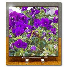 Purple flowers in a garden bend on gray, green leaves Desk Clock
