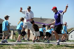 Brian Hepperle, third grade teacher, and Jeff Ingram, physical education teacher, encourage limbo dancing for Springs Ranch Elementary School students during a fundraiser walk May 17 at High Meadows Park in Falcon School District 49. More than 700 students, kindergarten-fifth grade, joined the effort to raise funds for a school gymnasium sound system. Many children received a donation to complete the 90-minute walk, while others earned pledges based on how many quarter-mile laps they…