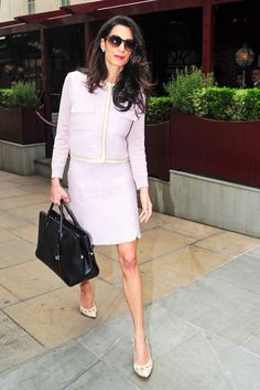 Amal Clooney wears a lilac Giambattista Valli skirt suit, sleek nude pumps, and a functional black tote