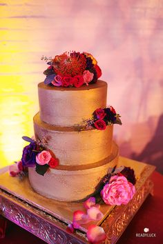 Three-tiered gold wedding cake with fresh flowers | Lindsay Hite of Readyluck | Brides.com