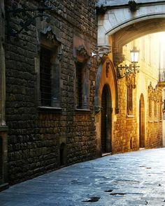 Barcelona Street in La Ramblas or Barri Gotic in the early morning light as the golden sun rises.