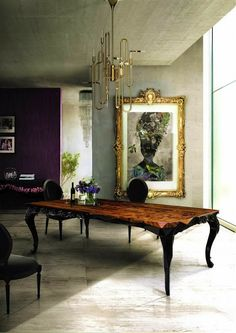 Modern art and chandelier against the antique frame and table. Stunning!