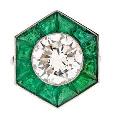 "Art Deco Diamond Emerald ""Halo"" Platinum Ring, c.1930. The center diamond weighs 4.0 carats. The 12 tile cut emeralds is 3.0 carats."