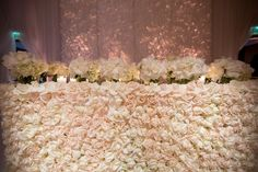 feathered back drop | sweetheart table covered in white roses | custom, mirrored stage | draped ballroom in sheer, white fabric | mirrored table tops, candles and soft lighting | tic-tock couture florals