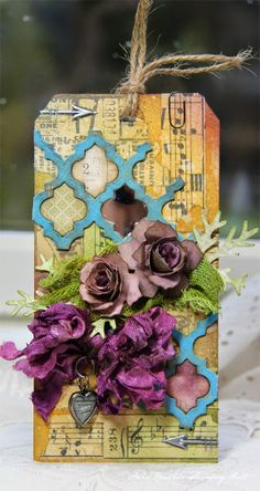 Perfect combination of Tim Holtz die, Prima flowers and great ribbon on a distressed art tag.  all it needs in one of Julie Nutting's new doll stamps.