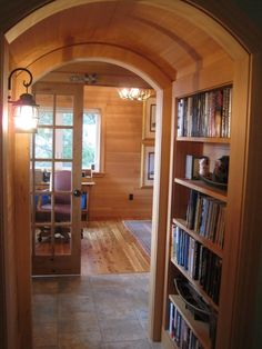 I think I have died and gone to beach cabin heaven...  I love this arched doorway covered in wood...  gorgeous!