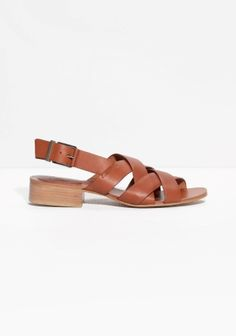 Wide cross-crossing straps detail these supple leather sandals featuring a buckled sling-back strap, all atop a comfortable stacked block heel.