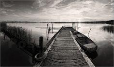 holzsteg am see mit fischerboot schwarz weiß