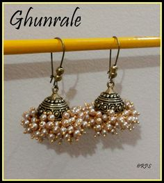 Bunches of gold finished glass pearls to beautify a simple jhumka frame. A little on the heavier side of earrings.... nothing can beat its royal look.