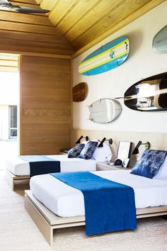 Surf inspired coastal bedroom decor with surf boards displayed as art