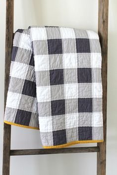 "grey gingham patchwork quilt - love the pop of yellow on the binding. Would make a simple ""man quilt""."