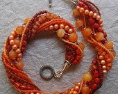 Hand knotted 13 strand, shades of tangerine and Bali sterling silver necklace