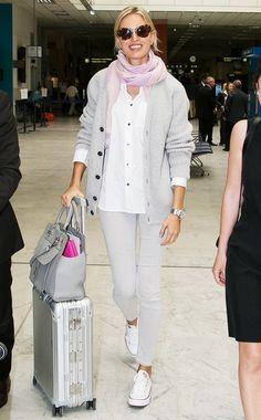 Karolina Kurkova wears a white button-down, gray cardigan, pink scarf, gray jeans, and Converse sneakers with Miu Miu sunglasses