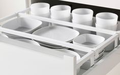 Close-up of open IKEA kitchen drawer. White tableware arranged with drawer dividers.