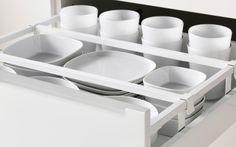 Nærbillede af en åben IKEA køkkenskuffe. Hvidt porcelæn organiseret med skuffeopdelere.