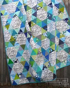 Today I am sharing a quilt that is being featured in Quiltmaker's May/June '14 issue! They coined this quilt Hex-a-doodle! It is made with triangles and half-hexagons, so there are no tricky y-seams! This blog seems to feature the same color palette for the last few quilts.... it is one of my favorites! Blue, green, teal, navy and lime scrappy triangles make up the hexagon rings that surround the hexagons. The hexagon centers areMenagerie Onyx from Sarah Watson's Indian Summer fabric line…