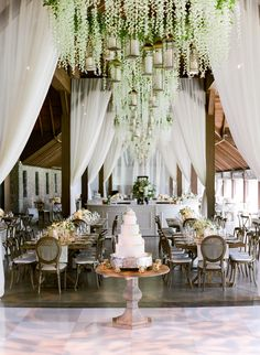 Stunning wedding reception space with dance floor, draping, and floral chandeliers.