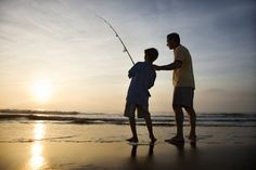 man teaching a young boy how to fish on the beach