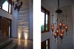 """O Hall de entrada com pé direito duplo traz na parede lateral um painel em pedra e a iluminação no piso de mármore  travertino nacional ressalta a beleza de um trabalho artesanal batizado de """"canjiquinha"""". No melhor estilo do Oriente, o lustre da Artefacto ilumina o hall com imponência e beleza para ninguém colocar defeitos. Suites, Chandelier, Ceiling Lights, Lighting, Interior, House, Design, Home Decor, Kitchen"""