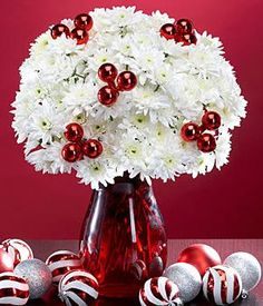"""Christmas floral arranegment.  """"This is just an awesome floral design because the mums will last at least two weeks if not longer and are the most affordable flower of them all. Change the water every three days or so and recut. You can make a """"pick"""" with any tall stick and some tape to tape the ornament to the pick and then pop it in your design..""""  #floral #design"""