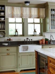 Historic Connection: Moss-green Shaker-style cabinetry creates a vintage aesthetic in this restored old-house kitchen. A rich glaze over the green paint adds to the patina. A porcelain farmhouse sink and beaded-board backsplash in crisp white also honor the vintage vibe and provide crisp contrast to the green trim and cabinets and the black countertop
