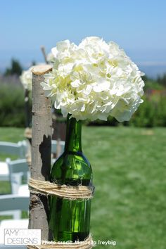 Recycled bottle with white hydrangea tied with twine. This is perfect for a rustic wedding ceremony! #rustic