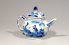 Delft Blue and White Chinoiserie Teapot and Cover  Delft, circa 1710  Painted on either side of the body with a Chinese figure standing in front of a pine tree feeding the ducks,  the spout and loop handle with scroll motifs and dots, and the cover decorated with floral sprigs and rock work, and surmounted by a conical knob.  Height: 12.6 cm. (5 in.)