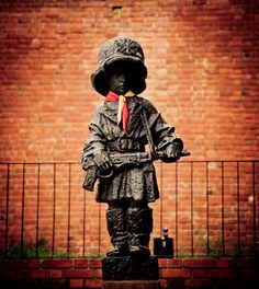 """Mały Powstaniec (the """"Little Insurgent"""") is a statue in commemoration of the child soldiers who fought and died during the Warsaw Uprising of 1944. It is located on Podwale Street, next to the ramparts of Warsaw's Old Town."""