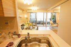 写真:対面式カウンターキッチンから見たリビングダイニング。家事をしながら部屋全体を見渡せるので子供のいる家族に安心(68平方メートル台タイプのモデル住戸)