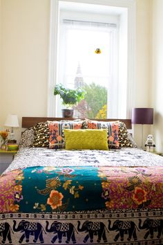 "As a textile designer (and lover of textiles) I tend to get very ""pattern-happy"" and the bedroom is a great place to indulge. The elephant tapestry by Magical Thinking from Urban Outfitters is the perfect base to add layers of color. The tapestry at the end of the bed is from a friend from her many travels, the two back pillow shams are Patch NYC for Target, and the front pillow is a little guy I made from scrap fabric."