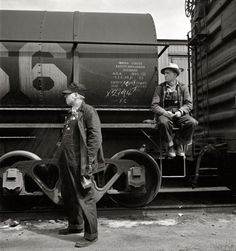 "March 1943. Barstow, California. ""Head brakeman J.C. Shannon (left) and swing brakeman B.E. Wilson waiting for their train to pull out of the Atchison, Topeka and Santa Fe yard."" Nitrate negative by Jack Delano."
