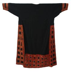 Dress (Thob) Size (cm):137 x 92 Saudi Arabia, Hijaz, Yanbu Date of object:1950's  Black thob with a wide and loose cut, side panels and inset sleeves. Decorated with very fine embroidery, covering the shaped side panels, back panel, small front panel and the deep cuffs on the sleeves. The stitches include chain, fly, open Cretan, in green, orange, white and blue thread. The designs include geometrical squares that represent the square prayer ground and minarets (worked in buttonhole stitch)