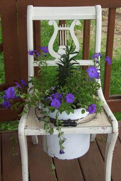 Flores em uma velha cadeira e panela de esmalte