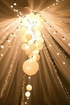 """Outdoor or indoor, this is gorgeous! All you need is tulle, round bulb string lights (or Christmas lights), paper lanterns, and you could use fishing line to hold it up!"""