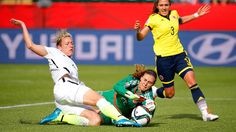 Abby Wambach #20 of the United States kicks the ball away from goalkeeper Catalina Perez #22 of Colombia