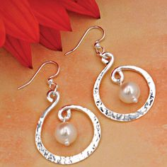 "Twirling Hoop Pearl Earrings. A single luminous pearl dangles from a dimensional swirl of silver plated jeweler's brass. Surgical Steel hooks.1 ½""L x 1""W. Handcrafted by Fair-trade."
