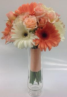 Coral and peach bridesmaid bouquet with gerbera daisies, roses and spray roses by Nancy at Belton Hyvee.