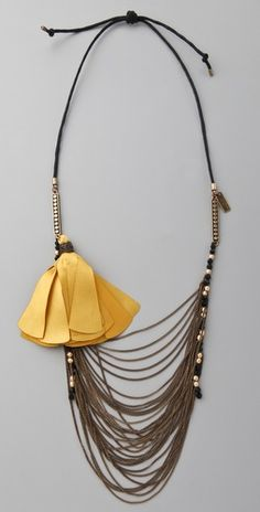 This cord necklace features a satin tassel and faceted beads at the brass chain tiers. Adjustable length.