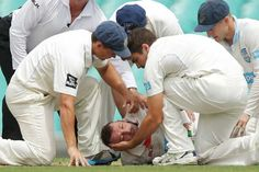 Phil Hughes on Ground and Players Holding Him