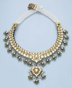 A MODERN INDIAN DIAMOND AND SEED PEARL NECKLACE   The table and rose-cut diamond scroll collar with pear-shaped pendant and emerald bead fringe to the similarly designed central pendant and seed pearl backchain, reverse decorated with red, white and green enamel, 41.3 cm. long